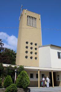 Foto: Hellgelber Kirchturm, oben flach mit Kreuz, weiter unten mit gitterartig angeordneten, kleinen runden Fenstern. Davor ein überdachter Säulengang.
