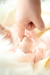 Baby mit geschlossenen Augen hält einen Erwachsenenfinger. Helles, freundliches Bild.