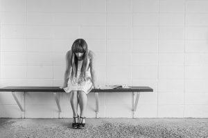 Eine Frau mit langem Haar sitzt auf einer Bank, die an an einer leeren Wand befestigt ist. Sie sitzt nach vorne gebeugt. Foto in Grautönen