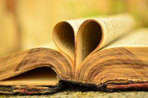 Ein altes Buch, liegend, obere Kante vorne ... einige Seiten sind zu einem Herz eingesteckt.