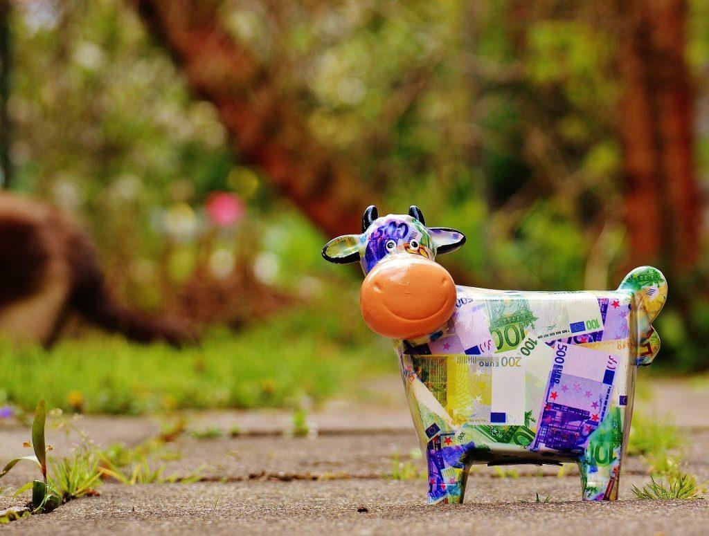 Eine Kuhfigur, die mit Geldscheinen beklebt scheint, steht auf Gartenfliesen vor Baumstämmen und Sträuchern