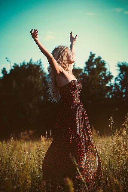 Frau in Kleid auf einer Wiese vor Bäumen hebt die Arme
