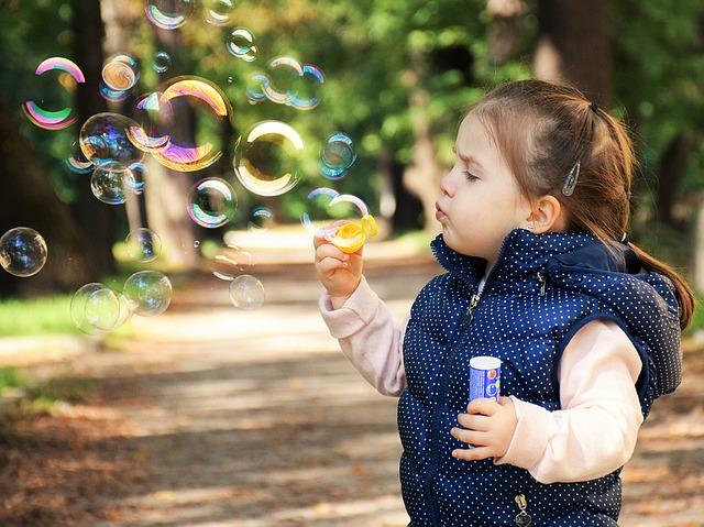 Ein kleines Mädchen steht im Wald und bläst Seifenblasen