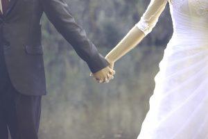 Links ein Bräutigam im Anzug, rechts eine Braut im Kleid halten einander an den Händen. Man sieht nur den Beginn ihrer Oberkörper und Teile der Beine.