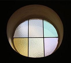 Ein rundes Glasfenster, mit Metallstangen in sechs Abschnitte unterteilt. Das Glas ist leicht gewellt und in blassen Pastellfarben: blau, rot, grün, gelb, blassgelb, rosa.
