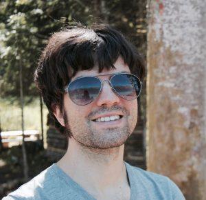 Junger Mann mit Sonnenbrille und schwarzen Haaren