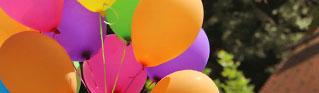 Orangene, violette, rosane, ein grüner und ein gelber Luftballon, zusammengebunden, schweben vor Bäumen und einem Dach.