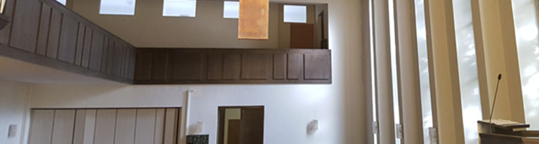 Rechts ein Mikrofon auf Pult, dahinter hohe Fenster, durch die Licht fleckt, auf Raum-Rückwand ein Balkon unter Fenstern