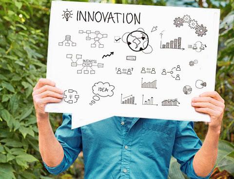 Mann vor Pflanzen hält ein Schild hoch, darauf gezeichnet Diagramme in schwarz-weiß ... oben links eine Glühbirne, daneben der Text: Innovation.